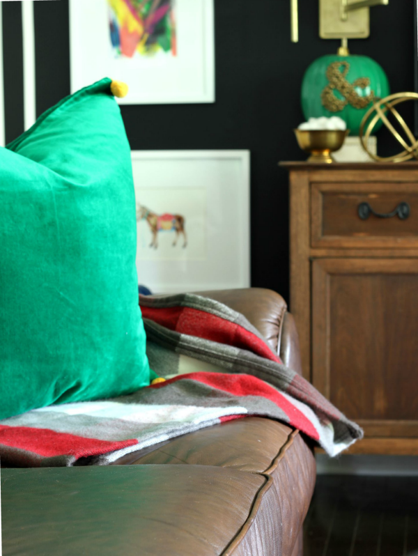 Decorating with Green: Green Pillow paired with Plaid Throw against a black wall.