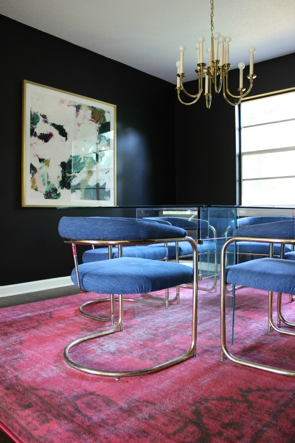 A STUNNING HOME! The 70's Landing Pad Home Tour: The Dining Room | Black and White Decor / Moody Interior Design / Vintage Interior Design / Glass Dining Table / Vintage Brass Chandelier / Vintage Round Cantilever Chairs