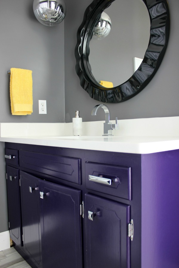 Such an adorable bathroom for a kid, but also stylish for adults! The 70's Landing Pad Hall Bathroom Remodel | Gray Walls / Black and White Decor / Kid's Bathroom / Purple Bathroom Vanity / Curvy Black Round Mirror / Retro Pendant Lights