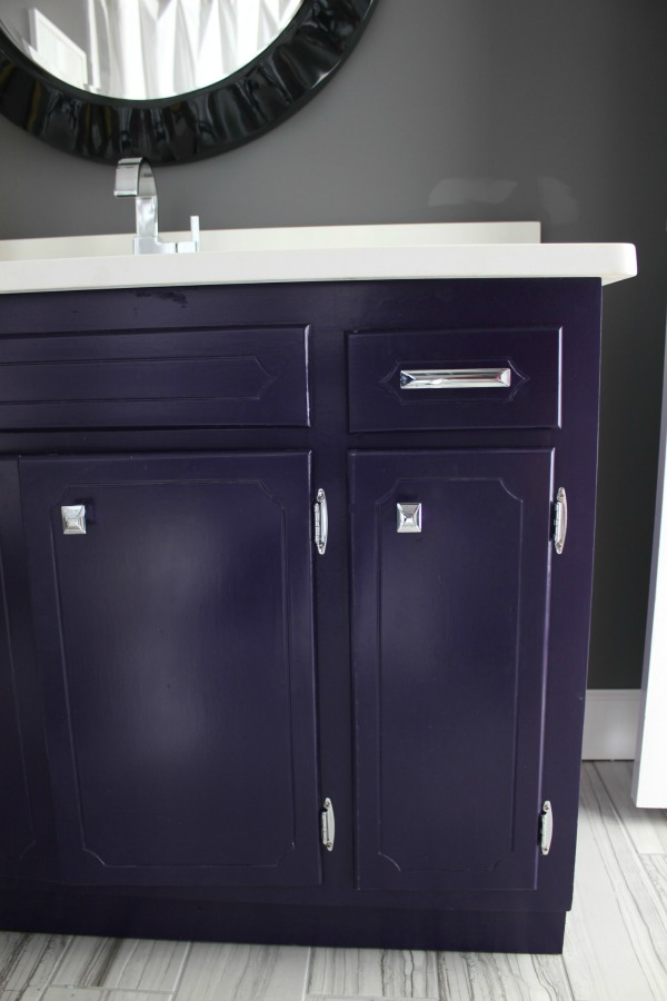 Such an adorable bathroom for a kid, but also stylish for adults! The 70's Landing Pad Hall Bathroom | Gray Walls / Black and White Decor / Kid's Bathroom / Purple Bathroom Vanity / Gray Rectangle Floor Tiles
