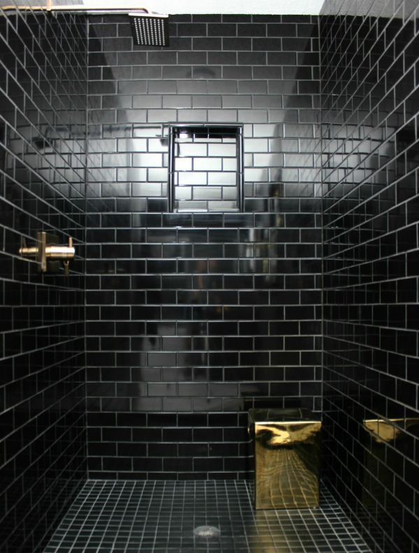 This bathroom remodel is gorgeous. It's a great combination of masculine and feminine design perfectly balanced. Black, Gray, and Brass Master Bathroom Remodel | Black Subway Tile Shower with Charcoal Grout | Brass Shower Faucet | Brass Stool for Shower | Masculine Bathroom