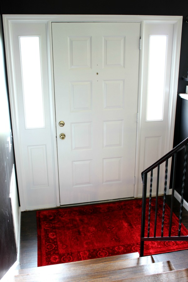 If you love black walls and dramatic interior design, you have to see this entryway makeover! It's full of deep moody colors and breathtaking art! Dramatic Entryway Makeover | Black Walls | All White Door | Dramatic Red Rug