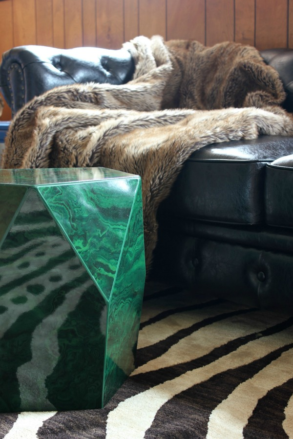 The Jungle Room Den Makeover inspired by Elvis' Jungle Room: They kept the paneling and it actually looks really good with the black trim! | Zebra Print Rug | Malachite Side Table | Black Leather Chesterfield couch | Fur Throw