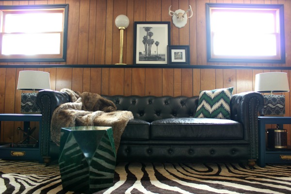 The Jungle Room Den Makeover inspired by Elvis' Jungle Room: They kept the paneling and it actually looks really good with the black trim! | Zebra Print Rug | Malachite Side Table | Black Leather Chesterfield couch