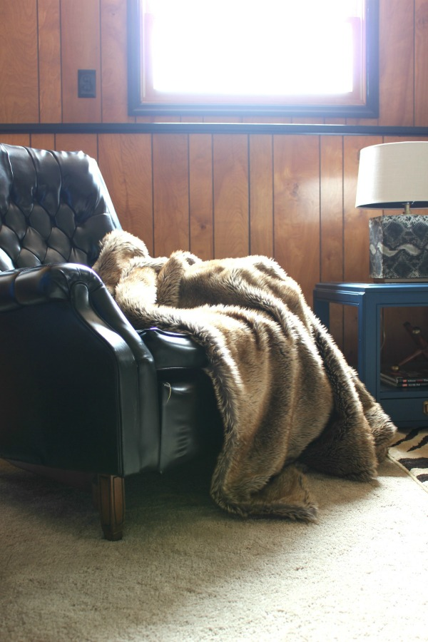 The Jungle Room Den Makeover inspired by Elvis' Jungle Room: They kept the paneling and it actually looks really good with the black trim! | Vintage Black Pleather Chair | Fur Throw