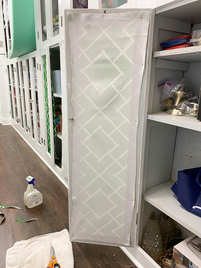 Cabinet Makeover - attaching upholstery fabric to the backs of cabinet doors.