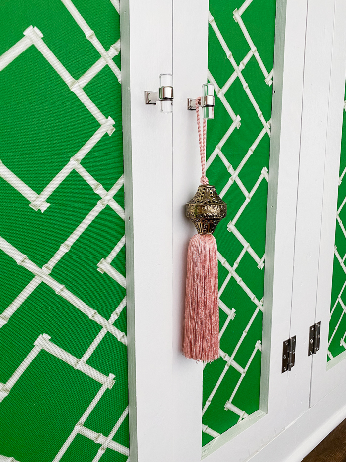 Mudroom storage cabinets with green and white lattice fabric and acrylic knobs.