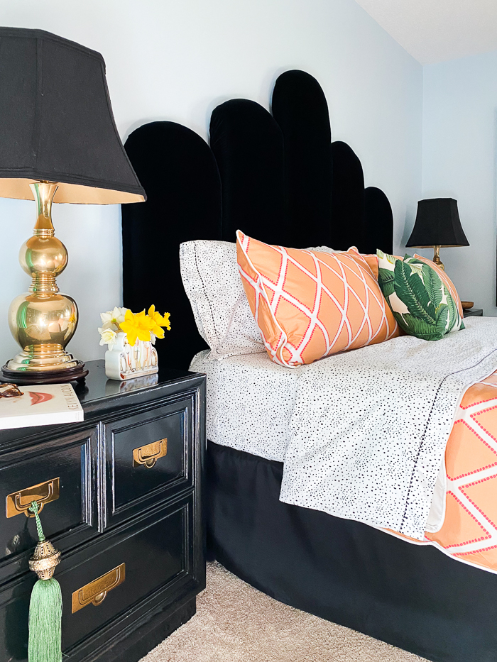 Home decorating projects you can do while you're stuck at home. Blue painted bedroom with black velvet headboard and orange bedding.