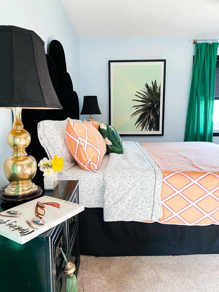 Bedroom with blue walls, orange bedding, black, white and green accents.