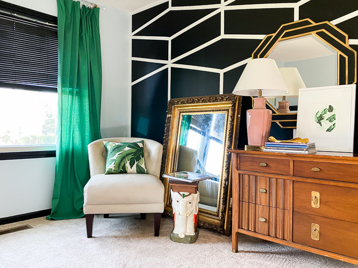Blue bedroom with green curtains, black and white accents.