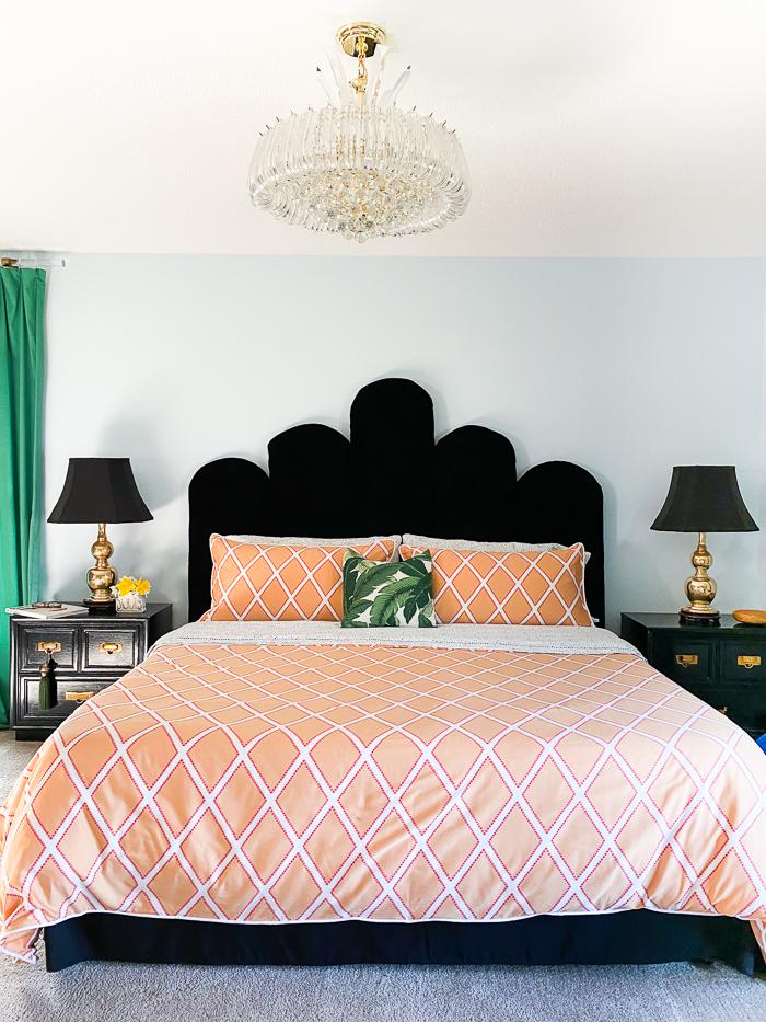 Bedroom with crystal chandelier, blue walls, black velvet headboard, orange bedding and green curtains.
